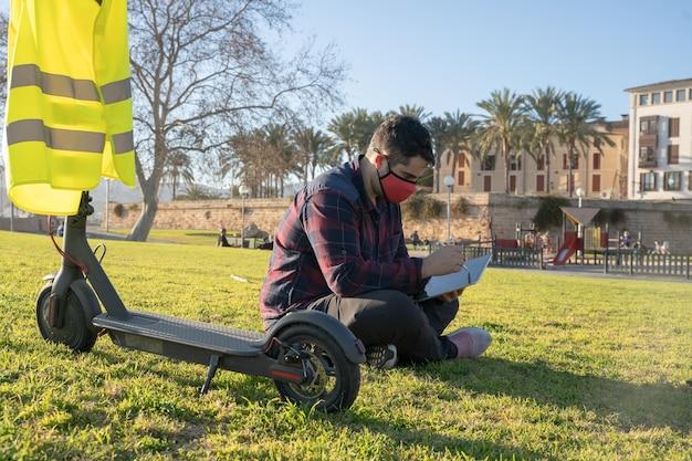 Un uomo con una maschera seduto sull'erba usando un tablet e uno scooter elettrico dietro di lui a palma di maiorca, spagna