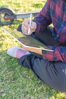 Un uomo con una maschera seduto sull'erba usando un tablet con una penna stilo e uno scooter elettrico dietro di lui a palma de mallorca, spagna (verticale)