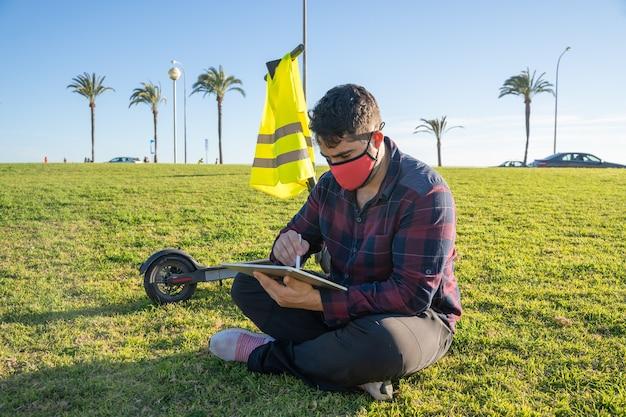 Un uomo con una maschera seduto sull'erba usando un tablet con una penna stilo e uno scooter elettrico dietro di lui a palma di maiorca, spagna