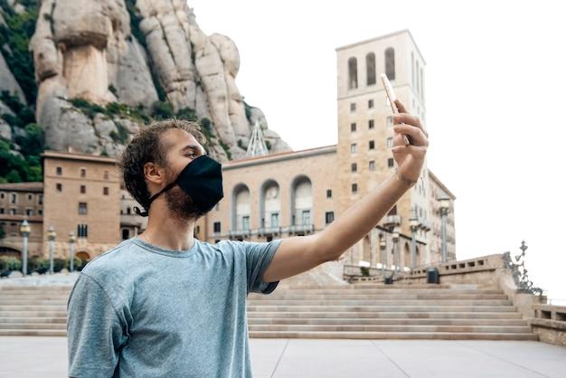 Uomo con la maschera di scattare una foto selfie nel monastero di montserrat, barcellona, spagna