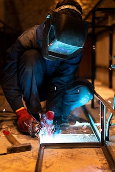 Uomo con maschera che salda metallo nell'atelier