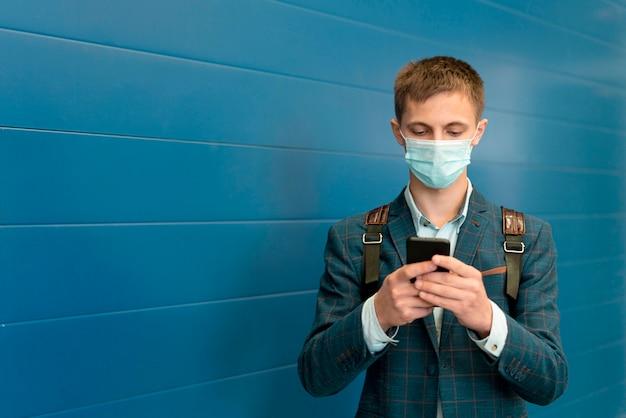 Uomo con maschera medica e zaino utilizza lo smartphone