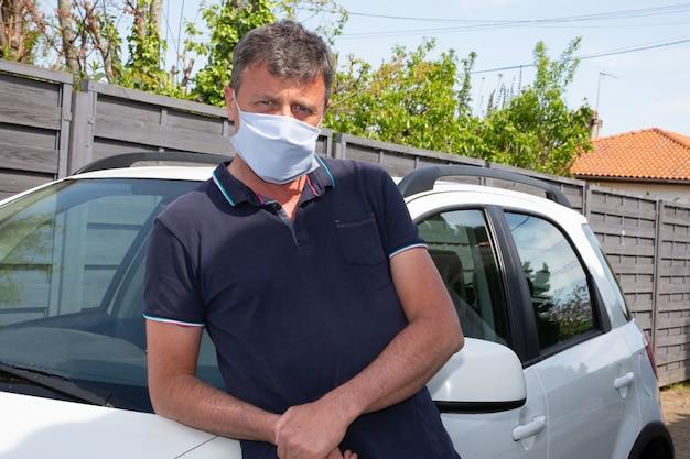 Uomo con maschera medica fatta in casa in piedi davanti all'auto virus covid-19 protezione coronavirus