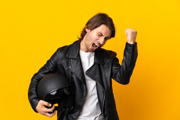 Uomo con un casco da motociclista isolato su giallo che celebra una vittoria