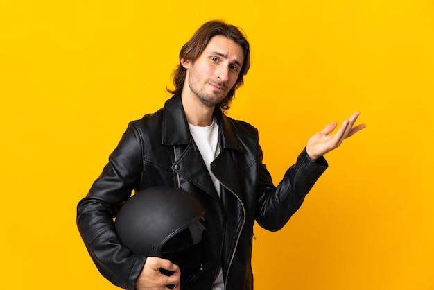 Uomo con un casco da motociclista isolato su giallo che allunga le mani di lato per invitare a venire