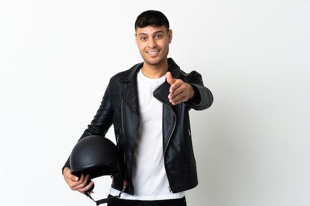 Uomo con un casco da motociclista stringe la mano per chiudere un buon affare