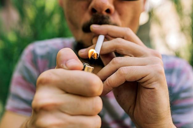 Uomo con baffi e barba accendere una sigaretta