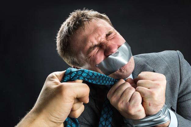 Uomo con la bocca coperta da nastro adesivo