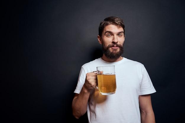 Uomo con un boccale di birra in uno stile di vita di emozioni di t-shirt bianca ubriaco sul buio