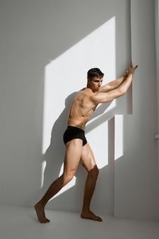 Uomo con un corpo muscoloso in mutandine nere in posa