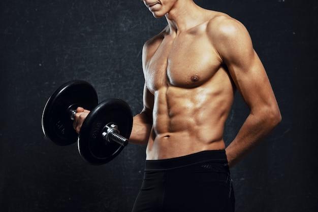 Un uomo con un torso nudo gonfio si copre con un asciugamano fitness bodybuilders