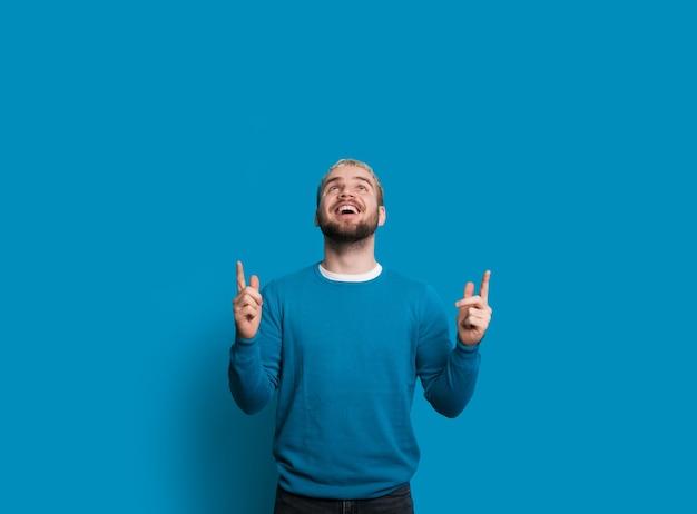 L'uomo con una bella barba sta indicando e guardando in alto