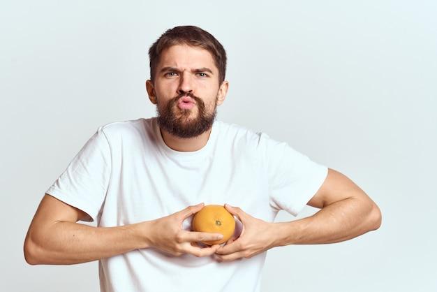 Uomo con un'arancia in una maglietta bianca isolata