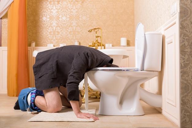 Uomo con i pantaloni abbassati malato nel water. interno del bagno in stile vantaggioso