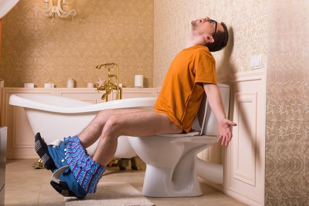 Uomo con i pantaloni abbassati seduto sulla tazza del water. interno del bagno in stile retrò