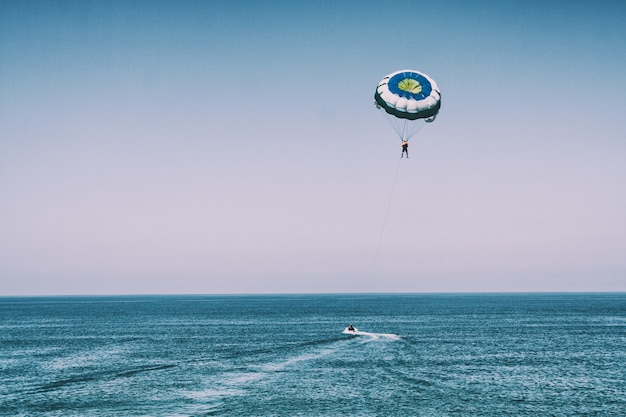 Uomo con paracadute in riva al mare