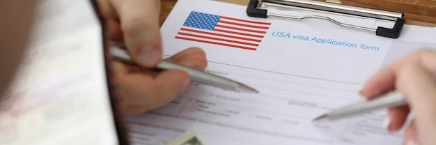 Uomo con passaporto e punti di dollari con la penna ai documenti nella cartella dell'ambasciata