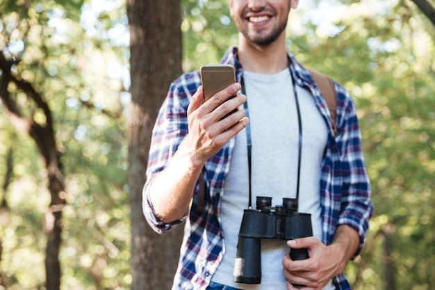 Uomo con il telefono nella foresta