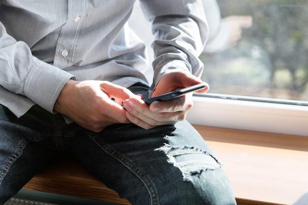 Un uomo con un telefono in mano siede vicino alla finestra