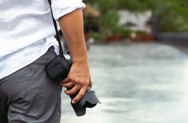Uomo con la macchina fotografica della foto fashion travel lifestyle natura all'aperto sulla luce del sole