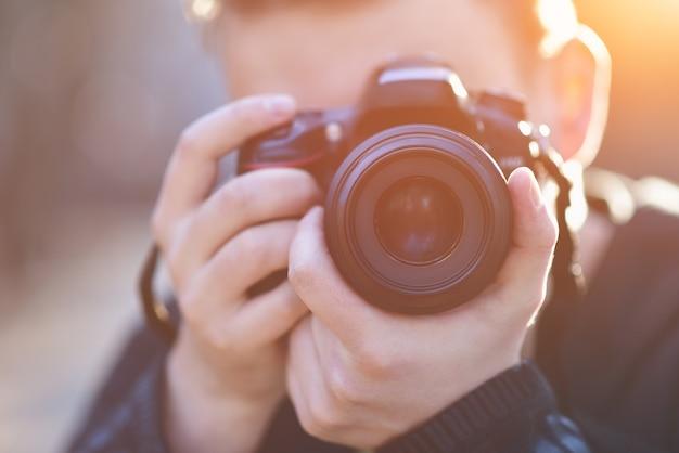 Uomo con macchina fotografica fashion travel lifestyle all'aperto stando in piedi