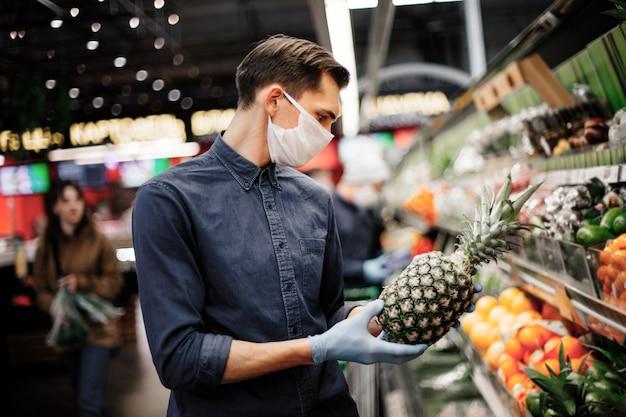 Uomo con un ananas in piedi vicino al bancone con frutta.
