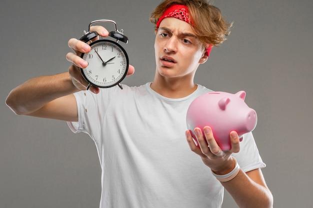 Uomo con un simpatico salvadanaio rosa e una sveglia nelle sue mani su uno sfondo grigio.