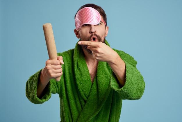 Un uomo con una mascherina rosa per dormire tiene in mano un mattarello