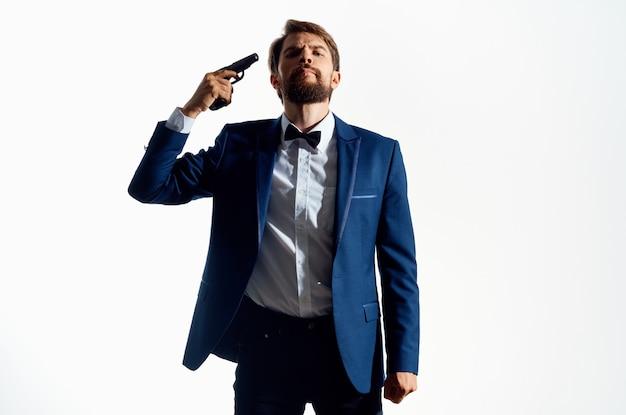 Uomo con una pistola in mano criminale detective killer sfondo chiaro