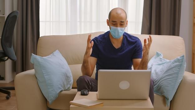 Uomo con maschera di protezione durante una videochiamata aziendale durante il covid-19.