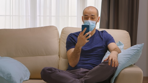 Uomo con maschera di protezione durante l'isolamento del coronavirus durante una videochiamata con la sua famiglia.