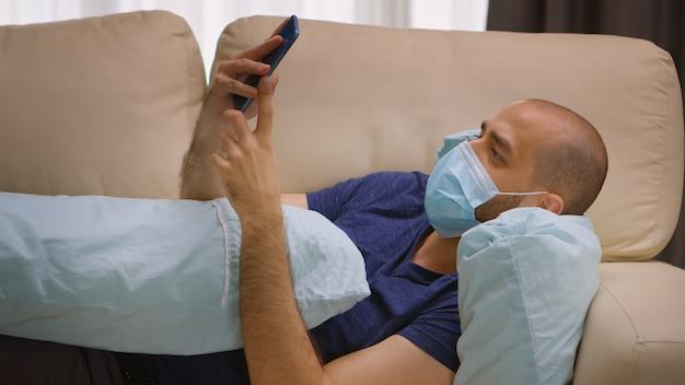Uomo con maschera di protezione durante il blocco del coronavirus che scorre sullo smartphone mentre abbraccia un cuscino.
