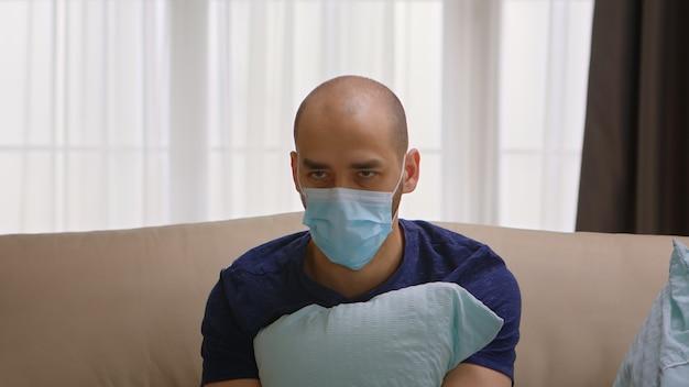 Uomo con maschera di protezione che ha un attacco di panico durante il blocco del coronavirus.