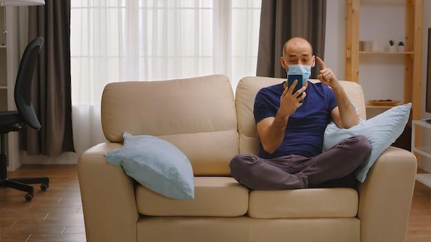 Uomo con maschera di protezione che fa una videochiamata con i suoi amici durante il blocco del coronavirus.