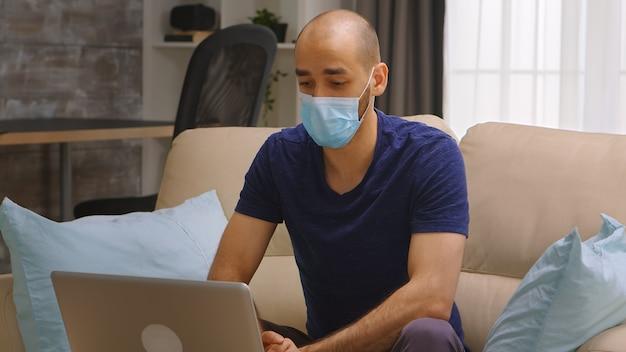 Uomo con maschera di protezione che ondeggia durante una videochiamata sul laptop. autoisolamento del coronavirus.