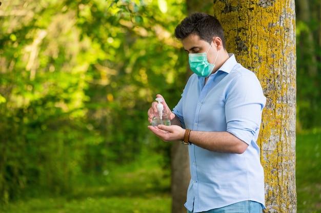 Uomo con maschera protettiva in piedi nel parco, usando il gel lavamani, contro la malattia di coronavirus covid-19. concetto di antisettico, igiene e salute. Foto Premium