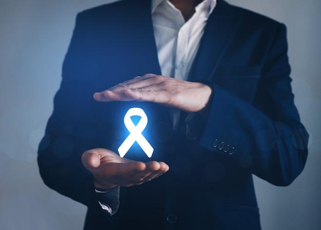 Uomo con mano protettiva che tiene nastro digitale per sostenere le persone che vivono e la malattia. concetto di giornata mondiale del cancro.