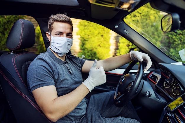 Uomo con maschera protettiva e guanti alla guida di un'auto. epidemia. stai al sicuro mostrando i pollici in su.