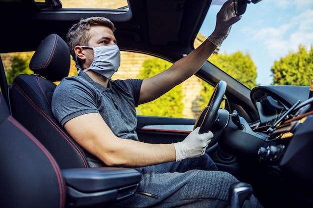 Uomo con maschera protettiva e guanti alla guida di un'auto. epidemia. rimanga sicuro.