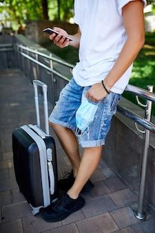 Uomo con maschera protettiva in mano, in piedi nel parco all'aperto con una valigia e un telefono cellulare, vita durante la pandemia di coronavirus, apertura del viaggio aereo, concetto di viaggio.
