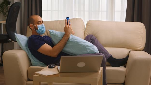 Uomo con maschera protettiva sdraiato sul divano che esegue affari dal suo telefono durante il covid-19.