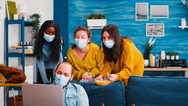 Uomo con maschere protettive in possesso di laptop guardando film commedia con razze miste divertirsi, ridere, mangiare snack mantenendo le distanze sociali per prevenire la diffusione del coronavirus durante la pandemia globale