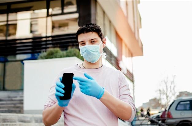 Uomo con abbigliamento medico protettivo utilizza lo smartphone a piedi nella strada della città.