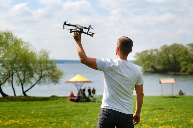 Un uomo con un quadricottero in mano, alzato al cielo in natura. Foto Premium