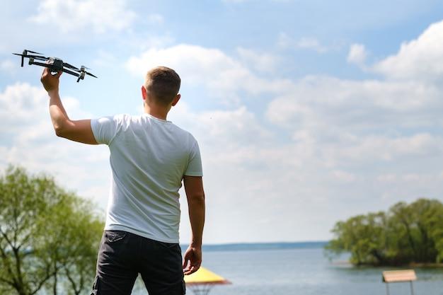 Un uomo con un quadricottero in mano, alzato al cielo in natura.