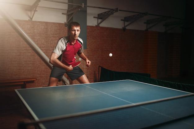 Uomo con la racchetta in azione, giocando a ping pong. ping pong training, sport ad alta concentrazione