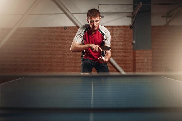 Uomo con la racchetta in azione, giocando a ping pong