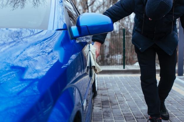 Un uomo con uno straccio per asciugare l'auto. concetto di autolavaggio