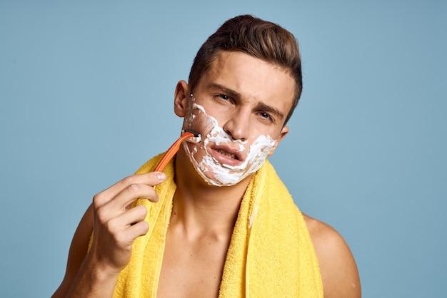 Uomo con rasoio e schiuma bianca per la rasatura