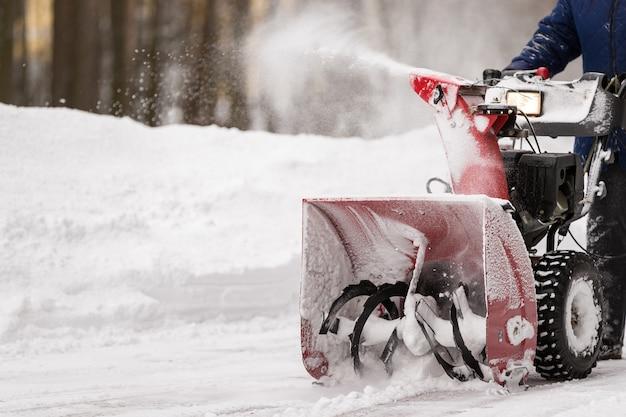 Un uomo con uno spazzaneve rosso coperto di neve libera l'area dalla neve